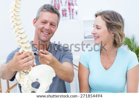 Physiotherapist showing spine model to his patient in medical office - stock photo
