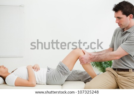 Physiotherapist sitting while massaging a knee in a room - stock photo
