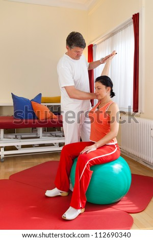 Physiotherapist standing behind a woman seated on a medical or pilates ball etending her arm and bending it backwards to maintain flexibility and movement in the shoulder - stock photo
