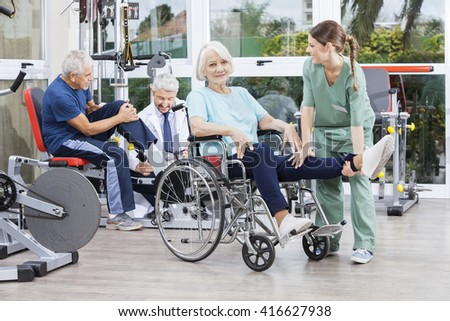 Physiotherapists Guiding Senior Patients To Exercise At Rehab Ce - stock photo