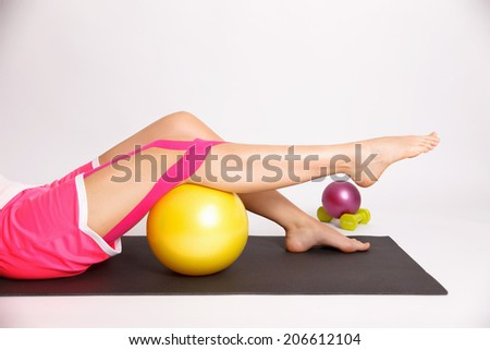 Physiotherapy for knee injury with ball and kinesiology tape - stock photo