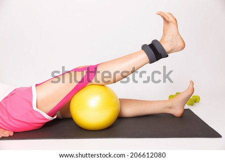 Physiotherapy for knee injury with kinesiology tape and foot wei - stock photo