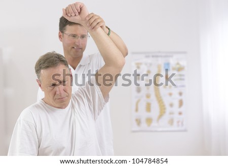Physiotherapy: Senior man and physiotherapist at office - stock photo