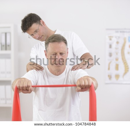Physiotherapy: Senior man doing exercise under supervision of physiotherapist - stock photo