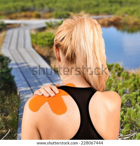 Physiotherapy treatment with therapeutic tape for shoulder pain, aches and tension. It is also used for prevention and treatment in competitive sports.Autumn Park Backgroun - stock photo