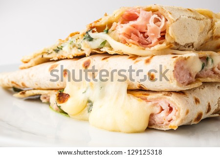 Piadina( Italian flatbread, typically prepared in the Romagna region)  slices with cheese, ham and arugula. - stock photo