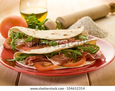 piadina with ham arugula and tomatoes, typical italian sandwich - stock photo
