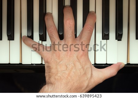 Pianist hand playing a chord on a keyboard, high angle view.