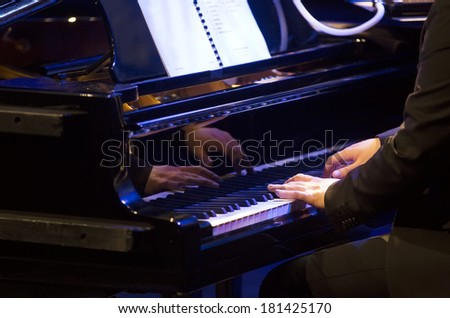 Pianist playing on piano - stock photo