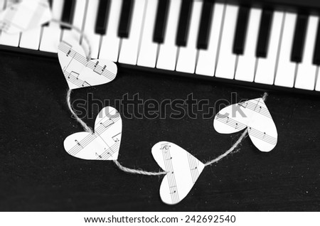 Piano keys and hearts of the music on a black background. I love music concept. - stock photo