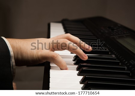Piano keys and human hand close-up
