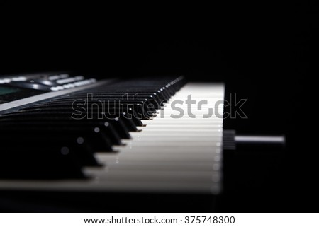 Piano keys in shadow on black background - stock photo