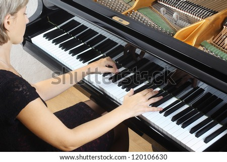 Piano pianist hands playing music. Musical instrument grand piano details with performer - stock photo