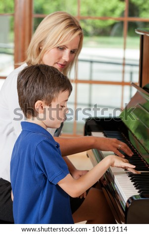 Piano teacher giving lessons to a young boy - stock photo