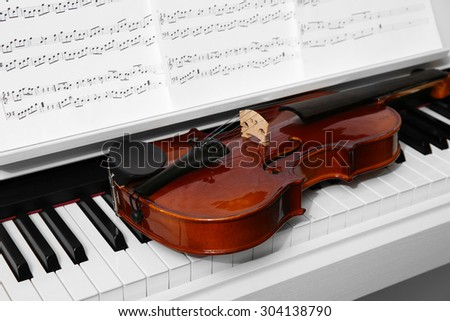 Piano with violin and music notes close up - stock photo