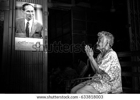 PICHIT, THAILAND - JANUARY 15 2016 old woman looking at image of Thailand's King Bhumibol Adulyadej with beautiful smile. at old market on January 15, 2016