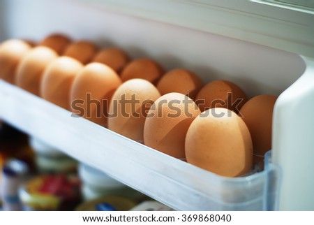 Pick chicken egg from the refrigerator, eggs on shelf of refrigerator - stock photo
