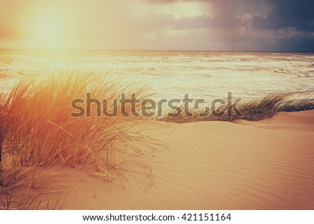 Pick elements of sun, sky, storm at a sea and sand dune, vintage style image - nature seascape background - stock photo