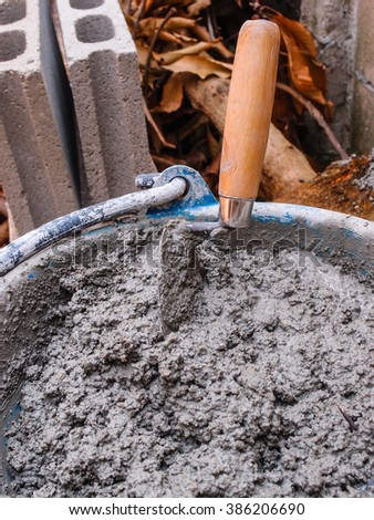 Pick up a trowel and cement mix concrete in bucket