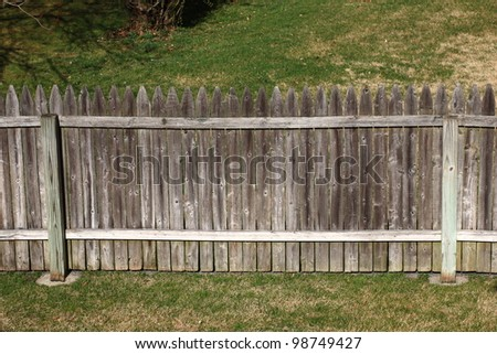 Picket Fence - Backyard fencing with wooden boards and green grass.