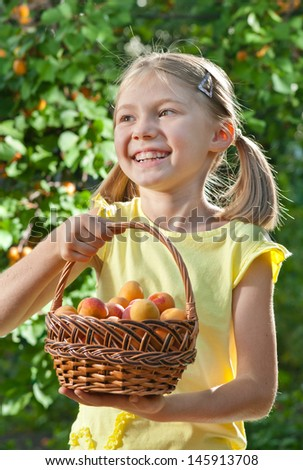 Picking apricots. Happy little girls holding basket with fruits - stock photo