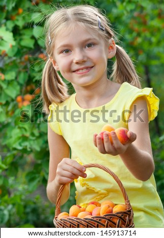 Picking apricots. Happy little girls holding fruits - stock photo