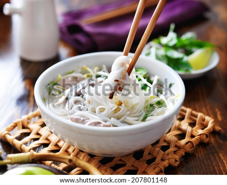 picking up noodles out of a bowl of pho - stock photo