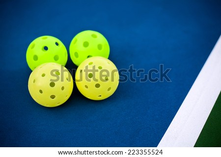 Pickleball balls on a pickle ball court - stock photo