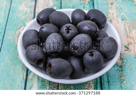 Pickled black olives fruit in white bowl over wooden background