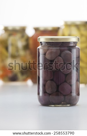 Pickled Black Olives Jar with Other Pickles Jars in Background - stock photo