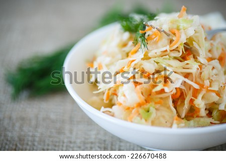 pickled cabbage and carrots in a white plate on the table - stock photo