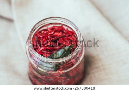 Pickled cabbage with beetroot and bay leaf in a small jar