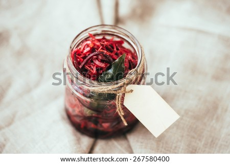 Pickled cabbage with beetroot and bay leaf in a small jar. Blank label provides copy space for a message - stock photo