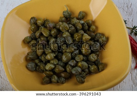 Pickled capers in the bowl on wood background