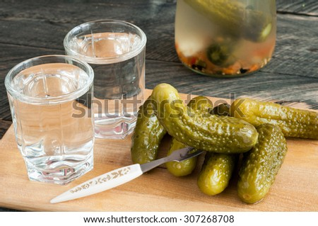 Pickled cucumbers and shot glass of vodka on wooden background. Rustic style. Selective focus  - stock photo