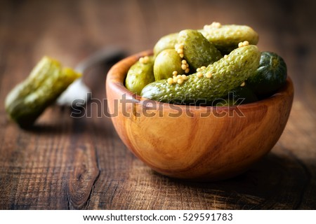 Pickled cucumbers in a wooden bowl with mustard seeds against dark rustic background