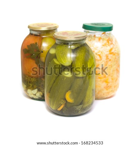 Pickled cucumbers, salted cabbage and tomatoes canned in glass jar on a white background