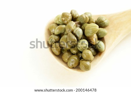 Pickled gourmet green capers in a wooden spoon