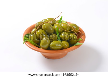 pickled greek olives, decorated with twigs and leaves - stock photo