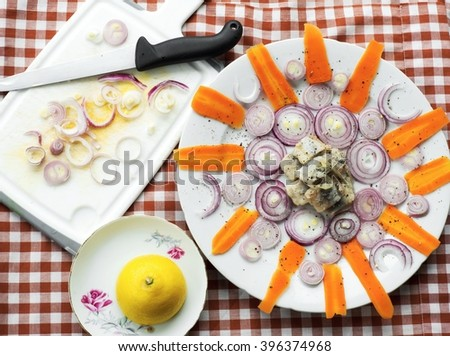 Pickled herring in circle of carrot stripe and onion circle on white plate, onion circle on kitchen board and knife, halved lemon, decorative food background  - stock photo