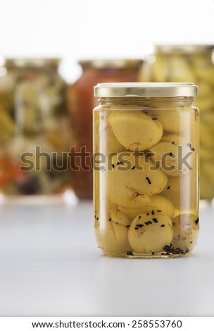 Pickled Lemon Jar with Other Pickles Jars in Background - stock photo