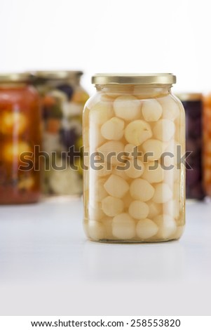 Pickled Onions Jar with Other Pickles Jars in Background - stock photo