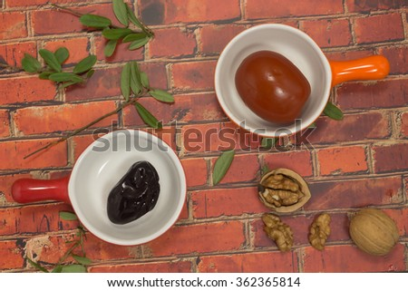 Pickled plums and tomatoes on the background of the brickwork. Walnut. Still life - stock photo