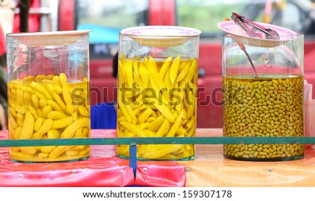 Pickled Tamarind and Mango in Bottle Glasses. - stock photo