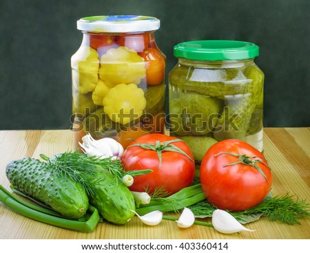 Pickled tomatoes and cucumbers in glass jars