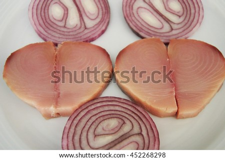Pickled tunny (Turkish: Lakerda) and onion on the dinner plate. - stock photo