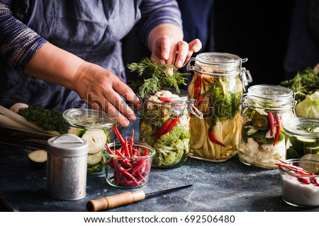 Pickled vegetables in jars displayed on table cauliflower broccoli bean cucumber green tomatoes fermented process glass jars variety copy space