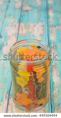 Pickled vegetables mix in mason jar over wooden background
