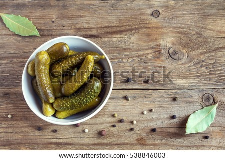 Pickles. Bowl of pickled gherkins (cucumbers) over rustic wooden background with copy space.