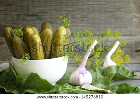 Pickles gherkins salted cucumbers still life on old planks - stock photo
